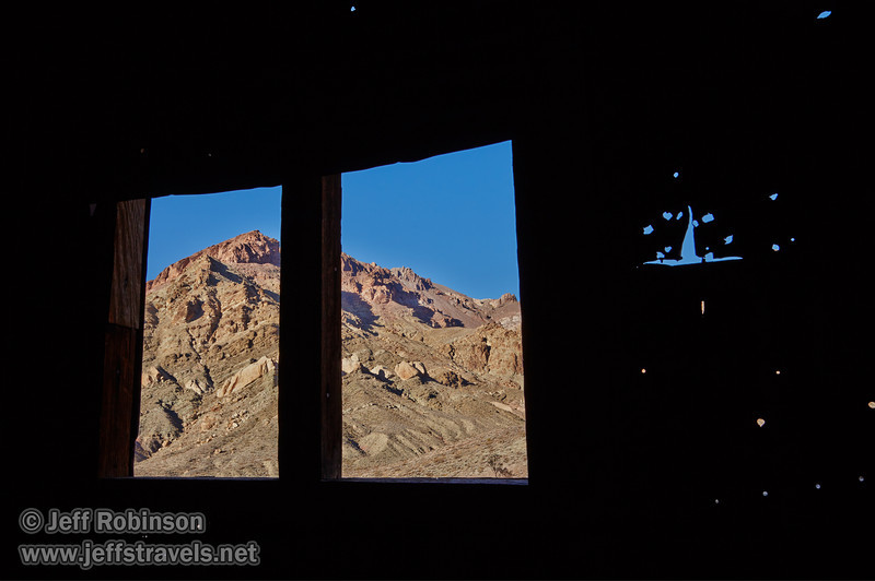 A pair of windows in an old building (with holes in the wall) frame a sunlit mountain side with hues of reds, browns, greens, and yellows under blue sky. (Sequence of photos for possible focus stacking.) (3/21/2013, Leadfield (ghost town), Titus Canyon Road, Death Valley NP)<br /> EF24-105mm f/4L IS USM @ 32mm f/16 1/100s ISO200