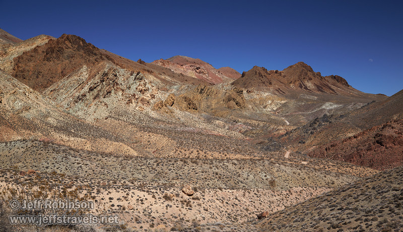 Titus Canyon Rd. looks small compared to the desert mountains with their reds, browns, yellows, and greens under deep blue sky, as the moon rises over the mountains. (3/21/2013, Titus Canyon Road, Death Valley NP)<br /> EF24-105mm f/4L IS USM @ 35mm f/9 1/250s ISO200