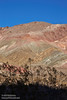 A colorful mountain with hues of reds, browns, yellows, and greens under blue sky, with a foreground silhouette of bushes. (3/21/2013, Leadfield (ghost town), Titus Canyon Road, Death Valley NP)<br /> EF24-105mm f/4L IS USM @ 84mm f/13 1/125s ISO100