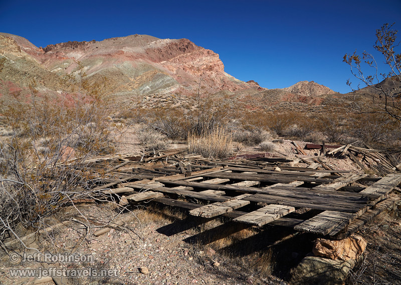 The remains of a wooden floor and foundation in the ghost town of Leadfield, with a background of a mountain with hues of greens, yellows, reds, and browns under deep blue sky. (3/21/2013, Leadfield (ghost town), Titus Canyon Road, Death Valley NP)<br /> EF24-105mm f/4L IS USM @ 24mm f/11 1/200s ISO400