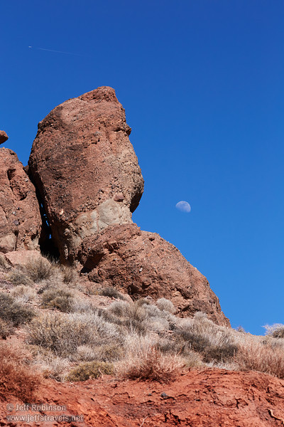 The moon in deep blue sky beside reddish rock formations and over the pale-green brush on the ground. (3/21/2013, Red Pass, Titus Canyon Road, Death Valley NP)<br /> EF100-400mm f/4.5-5.6L IS USM @ 150mm f/11 1/640s ISO400