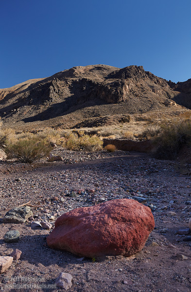 A dry stream bed with a large red boulder leads to a gray-green mountain with harsh shadows under blue sky. (3/21/2013, Leadfield (ghost town), Titus Canyon Road, Death Valley NP)<br /> EF24-105mm f/4L IS USM @ 45mm f/8 1/125s ISO400