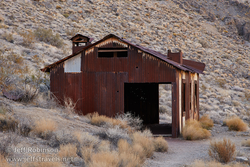 A rusted building (possibly yellow at one time) made of corrugated metal sits on a hillside with pale yellow and green desert plants around it. (3/21/2013, Leadfield (ghost town), Titus Canyon Road, Death Valley NP)<br /> EF24-105mm f/4L IS USM @ 105mm f/8 1/100s ISO400