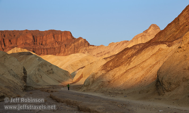 A person walks down the stream-bed-like canyon floor. The sides have yellowish colors in the nearer canyon, and on to the reds and browns of the rock layers of the farther wall pointing to the blue sky. The far-left canyon wall is dark red. (3/22/2013, Golden Canyon, Death Valley NP)<br /> EF24-105mm f/4L IS USM @ 65mm f/9 1/200s ISO200