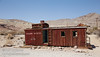 The remains of an old, red Union Pacific caboose converted into a building (there are no signs of wheels or tracks), with a large tank (water?) behind it. (3/22/2013, Rhyolite (ghost town), Death Valley trip)<br /> EF24-105mm f/4L IS USM @ 32mm f/10 1/320s ISO200