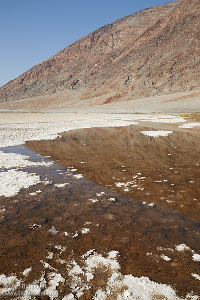 A yellowish-brown pond surrounded by white salt in Badwater Basin near the parking lot reflects patterns from the nearby mountains. (3/22/2013, Badwater Basin, Death Valley NP)<br /> EF24-105mm f/4L IS USM @ 28mm f/11 1/200s ISO100