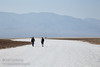 A westerly view of people walking on the white pathway in its S-shape across the browner and rougher salt pan that fills most of the basin. The hazy Panamint Range is in the background. (3/22/2013, Badwater Basin, Death Valley NP)<br /> EF24-105mm f/4L IS USM @ 85mm f/10 1/250s ISO100