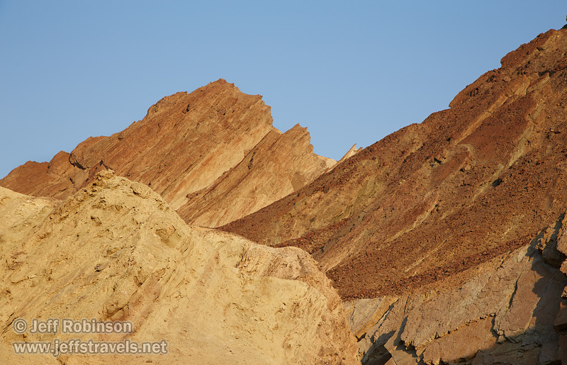 Canyon walls of angled rock layers with hues of yellow, red, brown, and green reach towards the blue sky. (3/22/2013, Golden Canyon, Death Valley NP)<br /> EF24-105mm f/4L IS USM @ 85mm f/10 1/200s ISO250
