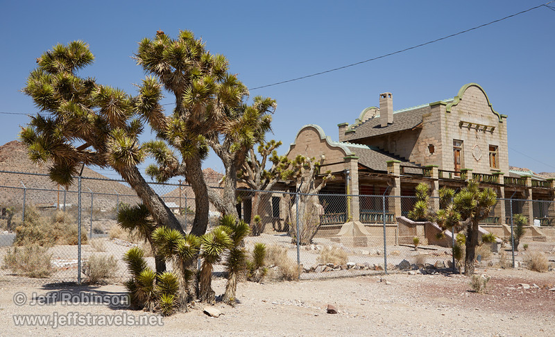 The old train station is surrounded by joshua trees. It is behind a fence, and appears to be in pretty good shape. (3/22/2013, Rhyolite (ghost town), Death Valley trip)<br /> EF24-105mm f/4L IS USM @ 40mm f/10 1/320s ISO200