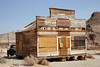 The Rhyolite Mercantile, boarded up and on wooden blocks (located near Tom Kelly's Bottle House), with an old truck behind it. (3/22/2013, Rhyolite (ghost town), Death Valley trip)<br /> EF24-105mm f/4L IS USM @ 60mm f/10 1/320s ISO160