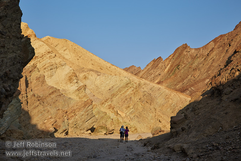 A couple walks through Golden Canyon, surrounded by sunlit cliffs with their hues of red, yellow, and green. (3/22/2013, Golden Canyon, Death Valley NP)<br /> EF24-105mm f/4L IS USM @ 58mm f/9 1/200s ISO125