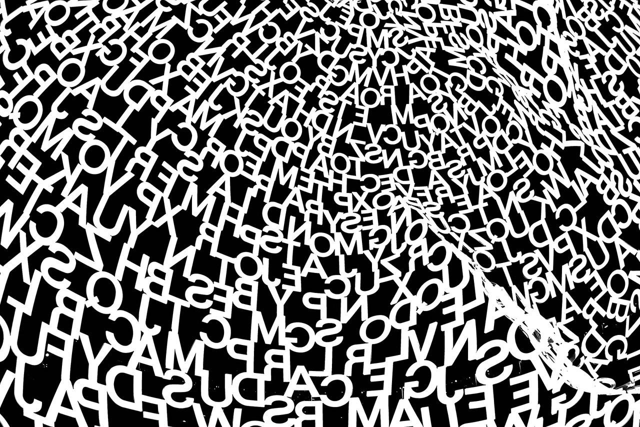 Composition diaphane constituée de lettres blanches, un géant fait de vide et de silence, dont le regard imaginaire embrasse l'immensité de la Méditerranée.