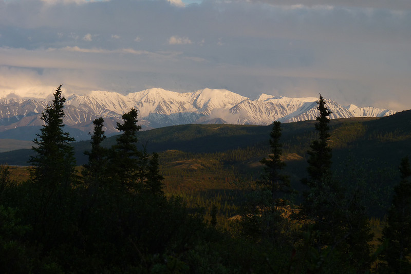 The foothills to the east of Denali are nicely illuminated, but the mountains behind them are still stuck in clouds.