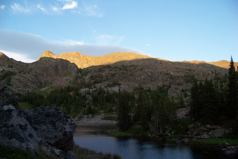The last gasp of sun illuminates the tallest mountain in the distance.