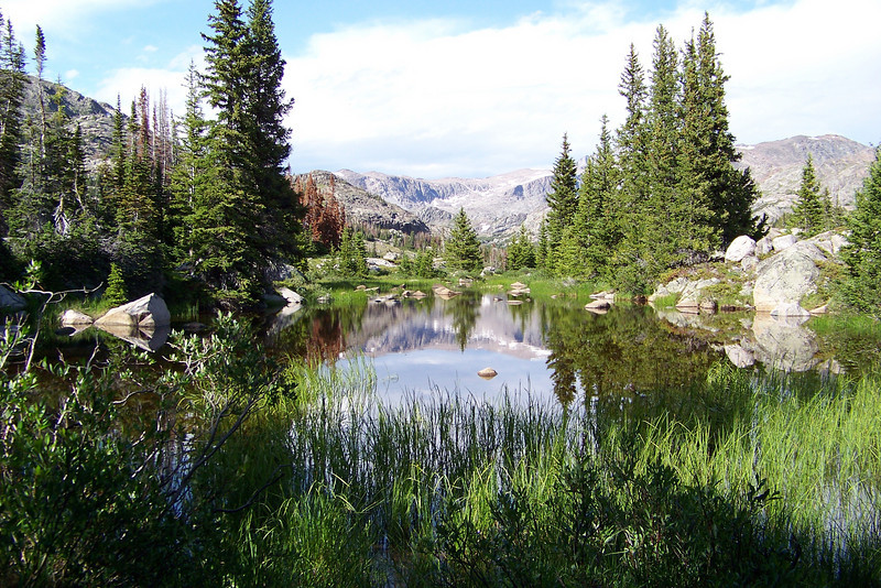 We pass a small pond that magically reflects the surrounding mountains.