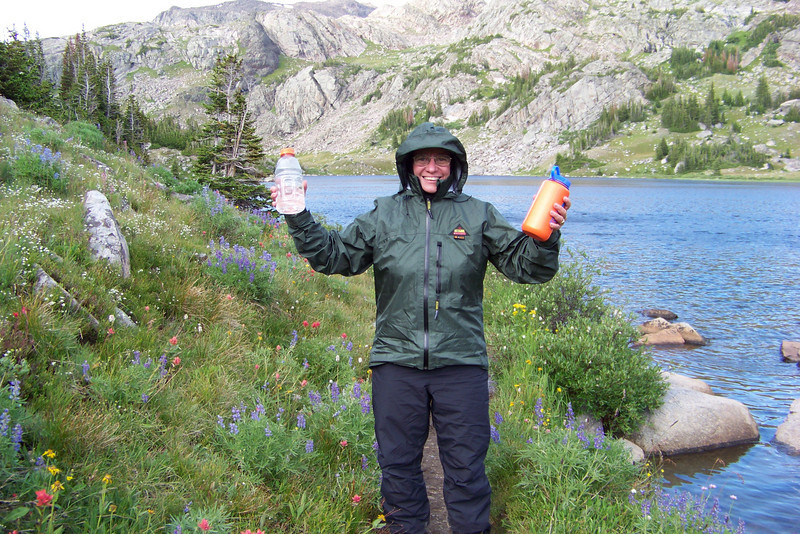 Jeane presents two full water bottles ready for dinner. The rain has left a chill in the air, so we're bundled up.