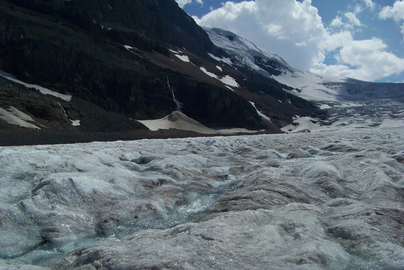 The ice has many small crevasses and rivulets of water running through it.