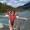 Our next stop along the Icefields Parkway is the Waterfowl Lakes.  Patti tries to hold her hat on in the breeze over a large river separating the upper from the lower lake.