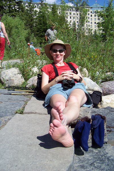 Patti, having had enough of iced feet, warms up on the Lake Louise Lizard Lounging Rocks.
