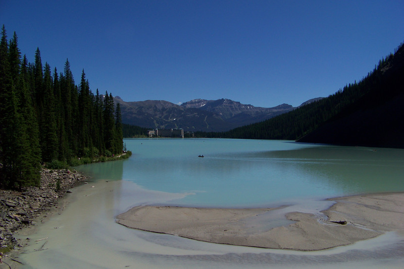 """We reach the far end of the lake (in the distance is the Chateau Lake Louise where we started).  The glacial melt flows into the lake at this end, depositing heavy silt.  The lake takes its color from the rock """"flour"""" suspended in it."""
