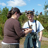 Jeane photographs while Patti gets lessons on how to hold the hawk.