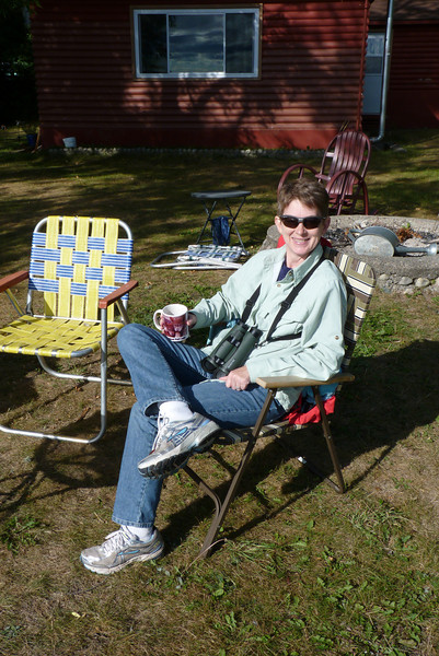 Patti sips her hot drink on the lawn of the cabin, overlooking White Iron Lake.