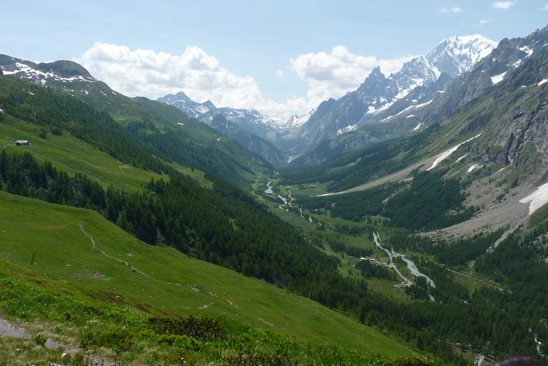 The glacial stream descends through the valley, colored a pale blue-gray from the silt.
