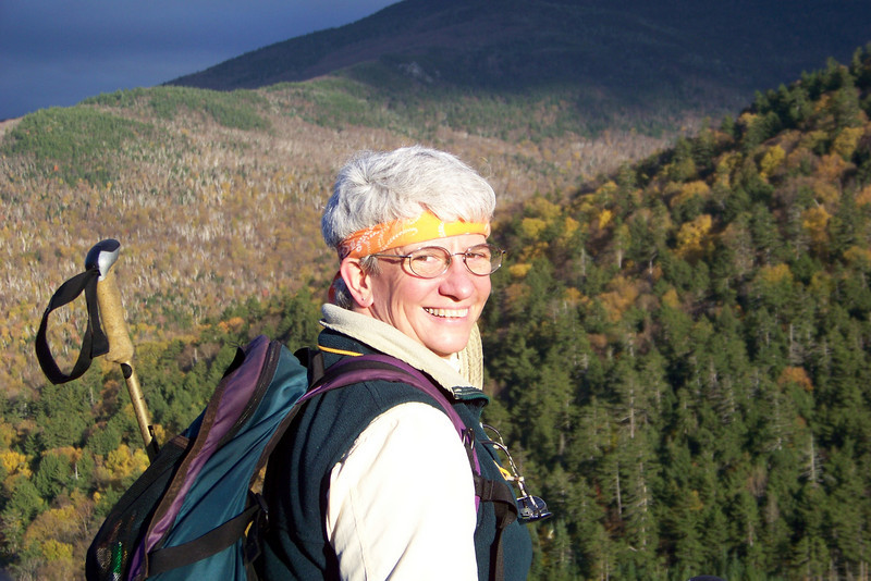 Jeane enjoys the fading evening light from Artist Bluff in Franconia Notch State Park.