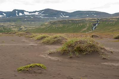 Bizarní krajina - písečná poušť v pozadí s vodopády a horami. Místo jak z jiného světa.
