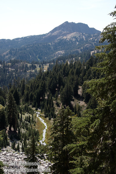 Sun reflecting off of Mill Creek (or something that feeds into Mill Creek) in an alpine valley with trees. Wide shot including background peaks (9/7/2009, Bumpass Hell Trail, Lassen NP)