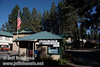 The Old Station Post Office with an American Flag above it and the motel and trees behind it (9/8/2009, Hat Creek Resort & RV Park, Lassen NF)