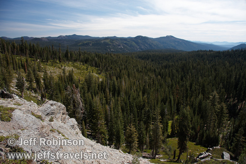 View down the valley with patches of green, lots of trees, and the mountain line. Seen from near the Cascade view point (9/10/2009, Kings Creek Falls hike, Lassen NP)