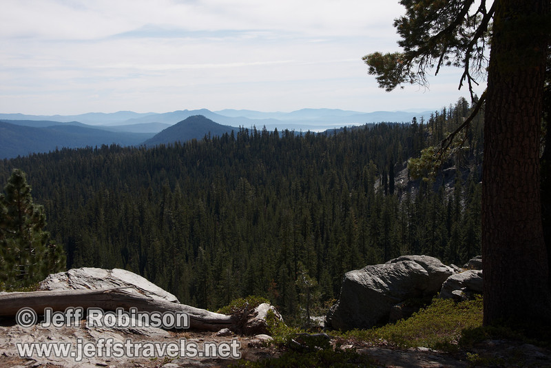 View of the mountains fading away through the haze, with forest and tree/rock framing in foreground. Seen from near the Cascade view point along the horse trail (9/10/2009, Kings Creek Falls hike, Lassen NP)