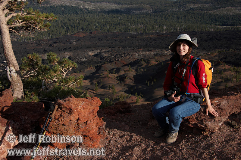 Lynda framed by trees, sitting on red rocks by the top of the southern trail entrance to Cinder Cone, with the Painted Dunes, Fantastic Lava Beds, Snag Lake, and Mountains in the background (9/11/2009, Cinder Cone hike, Lassen NP)