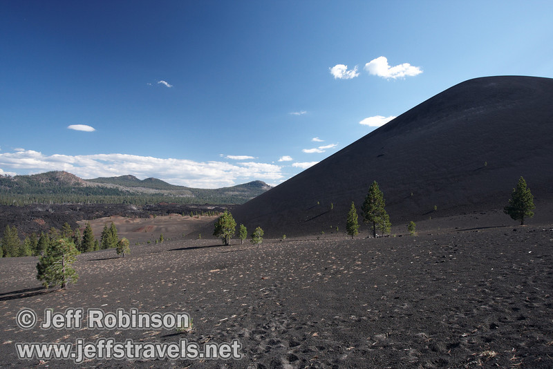 The left edge of Cinder Cone, with the Painted Dunes (mid-ground) and the Fantastic Lava Beds (background) in front of mountains to its left (9/11/2009, Cinder Cone hike, Lassen NP)