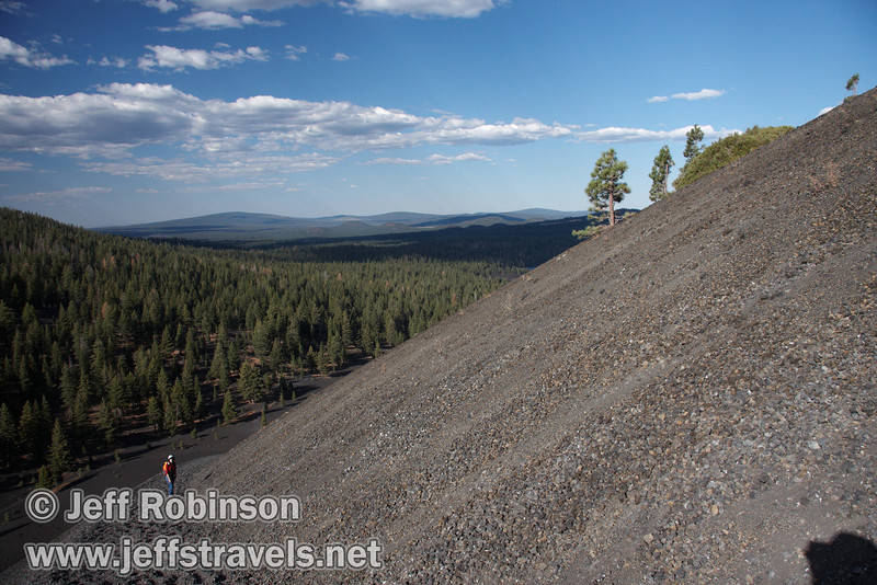 View of the side of Cinder Cone, with bushes and small trees growing on its side, and Lynda below on the 22 degree (40%) slope of the trail climbing up it (9/11/2009, Cinder Cone hike, Lassen NP)