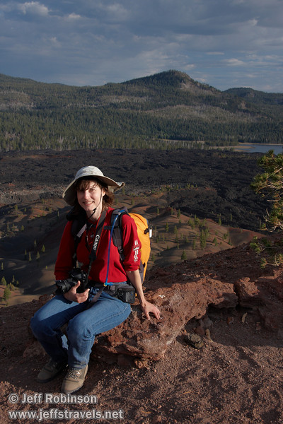Lynda sitting on red rocks by the top of the southern trail entrance to Cinder Cone, with the Painted Dunes, Fantastic Lava Beds, Snag Lake, and Mountains in the background (9/11/2009, Cinder Cone hike, Lassen NP)