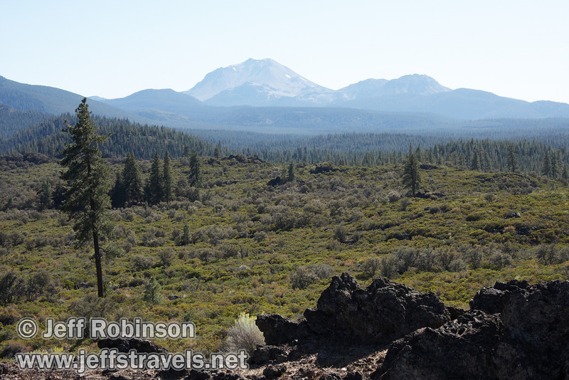 Distant Lassen Peak and Chaos Crags over the brush and trees, seen from a spatter cone past marker 11. (9/8/2009, Spatter Cones Nature Trail, Lassen NF)