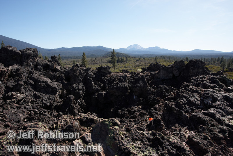 Lassen Peak and Chaos Crags over the lava of a spatter cone past marker 11. (Unfortunately, also over the orange cap of a drink bottle someone left) (9/8/2009, Spatter Cones Nature Trail, Lassen NF)