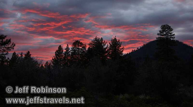brilliant red sunset over trees with Sugarloaf Peak on the right, seen from the trail to Subway Cave (9/12/2009, Subway Cave, Lassen NF, CA)