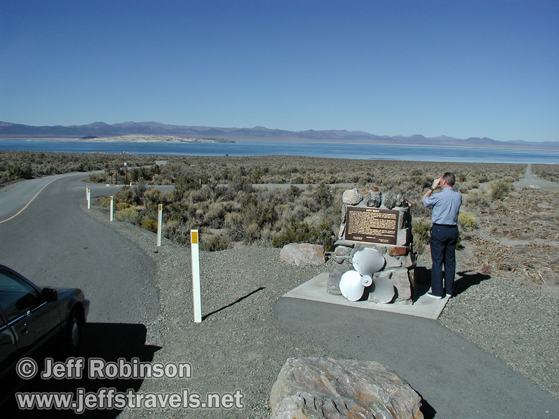 Dad taking video beside a Navy Beach sign, with the road to Navy Beach leading down to Mono Lake. The 1998 Accord is visible in the edge of the frame (Mono Lake 2002)