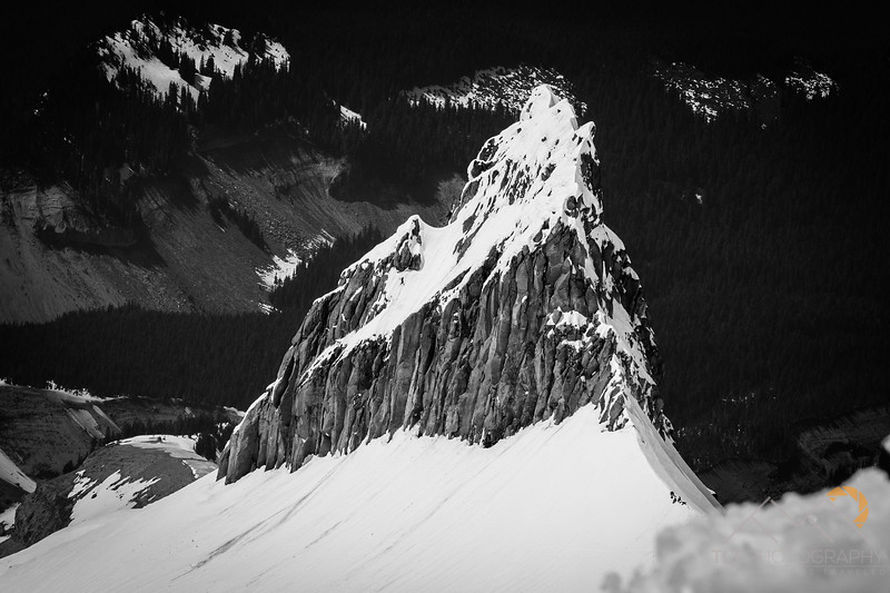 A sweet shot of Illumination Rock with skiers in the saddle below it from far above them on the crater rim of Hood above the Steel Clliffs.