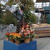 The statue of Fred Lebow (late founder of the NYC Marathon) is decorated with flowers.