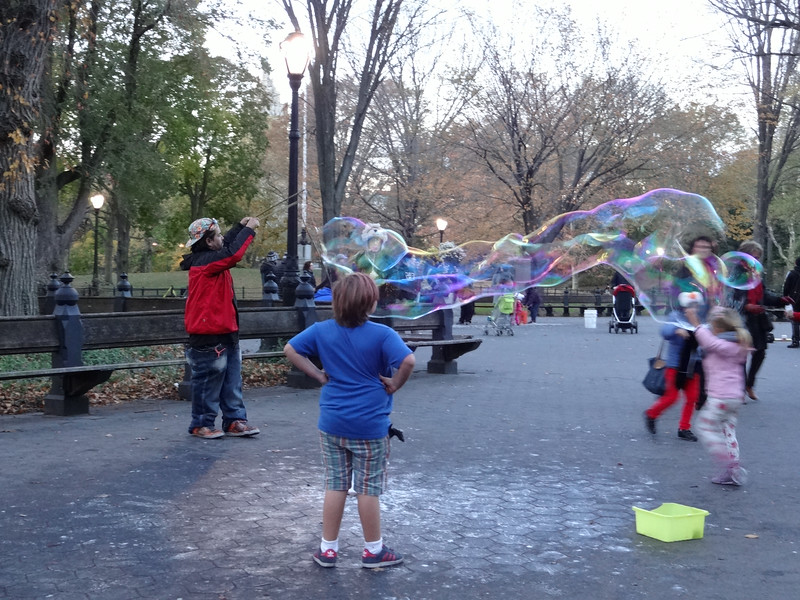 A fellow in the park is lofting up huge bubbles and the kids are enjoying them.