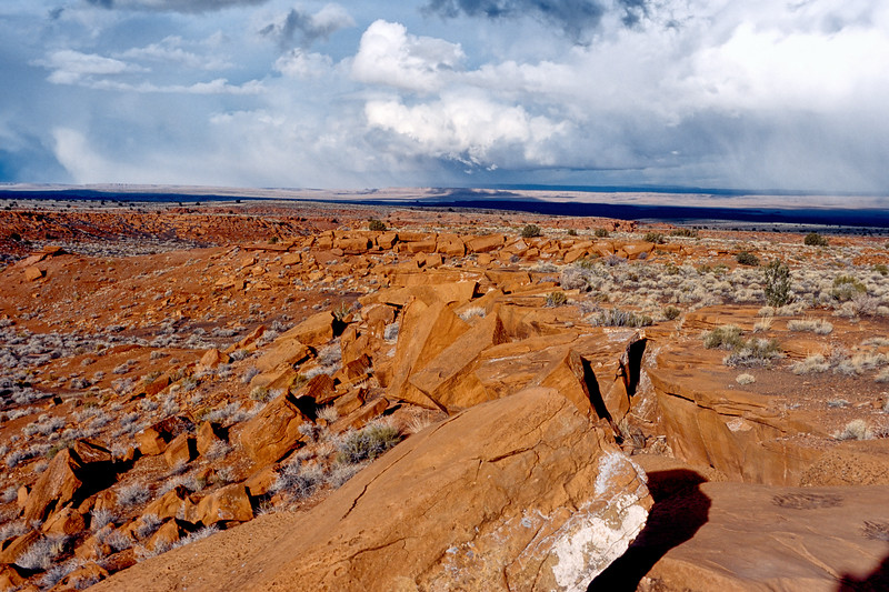 Looking north over the red rock-strewn plains of Arizona's Wupatki National Monument at boiling distant storm clouds.