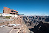"""The Grand Canyon West Skywalk building. The building sits in a magnificent location and its design blends nicely with the colors of the canyon but there's a big problem. Do you see it?  See that hideous offwhite slapdash wooden fence that's obscuring the ground floor and clashing with everything around it.  The fence looks even worse close up. It was obviously erected to cut off nice side views of the building and the skywalk loop. Without it, you could stand beside the building and get nice pictures of people on the loop with standard lenses. We cannot have that. Better ruin the aesthetics of the entire site so that marks, oops visitors, are forced to buy overpriced """"been there done that"""" shots by """"professional"""" loop photographers."""