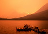 Many Glacier's Swift Current lake around sunset with a forest fire smoke..filled sky.