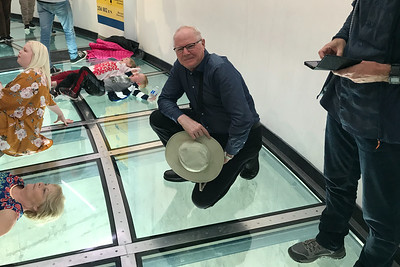 Me with Tilly hat in hand on the CN Tower glass floor. The tower glass floor is nice but it's not in the same league as the Grand Canyon West Skywalk.