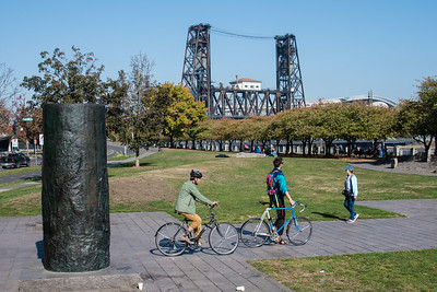 Cyclists passing by Portland park pillars.