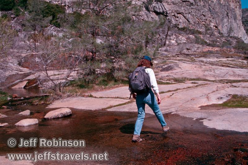 Lynda crossing a seasonal stream (on trail before Tueeulala Falls) (Wapama Falls hike, Hetch Hetchy, Yosemite NP, 3/30/2003 or 4/5/2003)